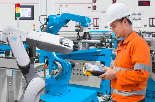 Ein Wartungsingeneur konntroliert die Roboter mit einem Handterminal.